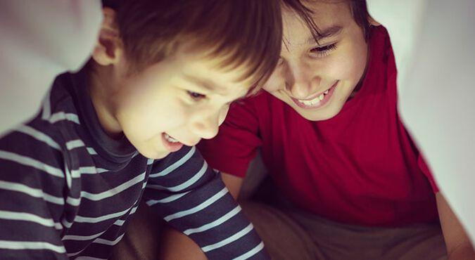 Niños jugando debajo de las cobijas